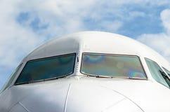 乘客飞机在蓝色的鼻子驾驶舱覆盖天空 免版税图库摄影