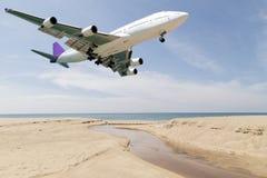 乘客飞机着陆、蓝天和海背景 库存图片