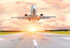 乘客飞机着陆和中断进场并复飞四处走动在跑道的日落 库存照片