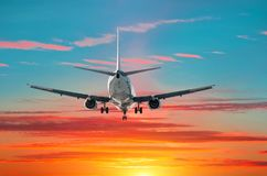 乘客飞机飞行着陆在蓝绿色梯度和红色天空背景的日落  免版税库存照片