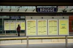 乘客读时间表在布鲁基火车站,比利时 免版税库存照片