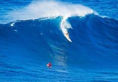 乘巨型波浪的冲浪者 库存照片