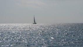 乘快艇与在海镇静大海的风帆  在天际的风船在美好的风景 因为背景是蓝色的小船小船可能棍打浮动旅馆图象略写法海洋红色风船航行风帆被传统化的使用的通知游艇黄色的黑暗的等标志 航行游艇 影视素材