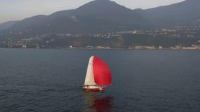 乘快艇与在Garda湖的红色风帆 意大利 股票录像