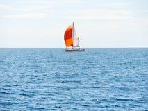 乘快艇与红色风帆在蓝色亚得里亚海 免版税库存图片