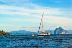 乘快艇在蓝色海、波浪、海天线、海峭壁和多云蓝天背景  免版税库存图片