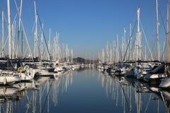 乘快艇小游艇船坞在一镇静天用蓝天和反射性水 免版税库存照片
