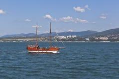 乘快艇稀薄的海角的背景的法老王在Gelendzhik海湾,克拉斯诺达尔地区,俄罗斯的 库存照片