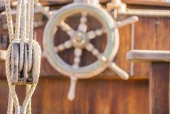 乘快艇,船舶滑轮和木舵在老帆船甲板转动 免版税图库摄影