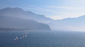 乘快艇 有游艇sailer船航行的风景全景由在平衡日落太阳光束的湖或海波浪 钓鱼炫耀 图库摄影