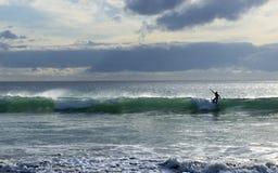 乘波浪的冲浪者 库存照片