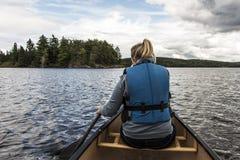 乘独木舟与在两条河湖的独木舟的女孩在安大略的加拿大阿尔根金族国家公园在晴朗的多云天 库存图片
