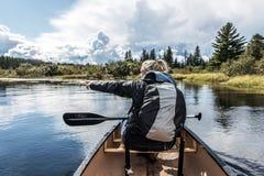 乘独木舟与在两条河湖的独木舟的女孩在安大略的加拿大阿尔根金族国家公园在晴朗的多云天 免版税库存图片