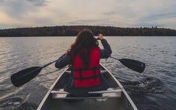 乘独木舟与在湖的银色独木舟的两个女孩在加拿大阿尔根金族国家公园在一晴朗的多云天 库存图片