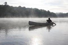 乘独木舟在一个有薄雾的湖的渔夫 免版税图库摄影
