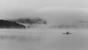 乘独木舟在黎明的人 免版税库存照片