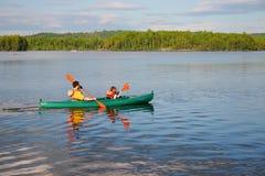 乘独木舟的父亲儿子 免版税库存照片