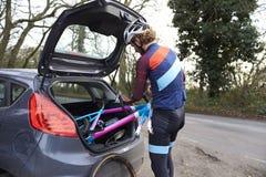 乘自行车的横越全国的骑自行车者在他的汽车外面后面  库存照片