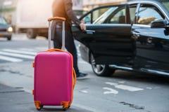 乘从机场的出租汽车和装载随身携带的行李袋子的人们对汽车 免版税库存照片