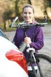 乘从机架的女性骑自行车者登山车在汽车 免版税库存图片