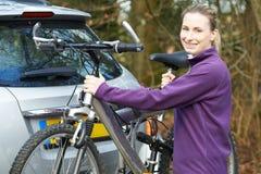 乘从机架的女性骑自行车者登山车在汽车 库存图片