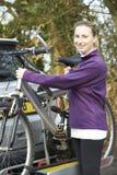乘从机架的女性骑自行车者登山车在汽车 免版税库存照片