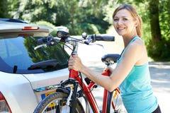 乘从机架的成熟女性骑自行车者登山车在汽车 库存图片