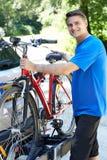 乘从机架的成熟男性骑自行车者登山车在汽车 图库摄影