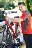 乘从机架的男性骑自行车者登山车在汽车 库存照片