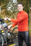 乘从机架的骑自行车者登山车在汽车 免版税库存图片