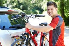 乘从机架的骑自行车者登山车在汽车 图库摄影