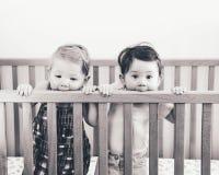 九个月的两个逗人喜爱的可爱的滑稽的小兄弟姐妹朋友黑白画象站立在床小儿床的 免版税库存照片