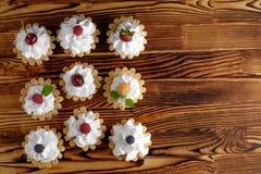 九个蛋糕用蛋白质在木桌上的奶油和夏天莓果 库存照片