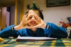 九岁的男孩画象有绿色冠的在家上色了h 库存图片