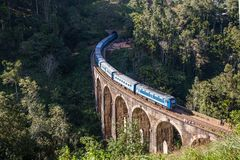 九曲拱桥梁和蓝色火车在斯里兰卡,埃拉 免版税库存图片