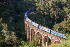 九曲拱桥梁和蓝色火车在斯里兰卡,埃拉 库存照片