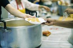 乞求食物的概念:捐赠食物帮助社会的人的朋友 库存照片