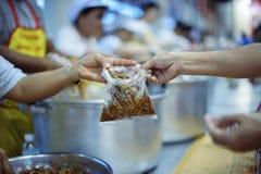 乞求食物的概念:捐赠食物帮助社会的人的朋友 免版税库存照片