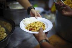 乞求食物的概念:捐赠食物帮助社会的人的朋友 图库摄影