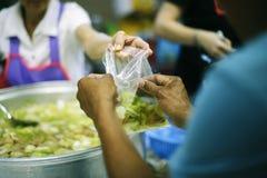 乞求食物的概念:捐赠食物帮助社会的人的朋友 免版税图库摄影