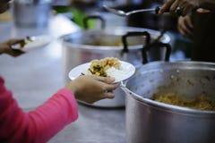 乞求食物的概念:捐赠食物帮助社会的人的朋友 库存图片