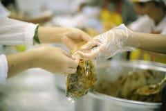 乞求食物的概念:捐赠食物帮助社会的人的朋友 免版税库存图片