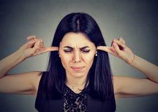 也是大量的噪音 塞住她的有手指的恼怒的少妇耳朵 免版税库存图片