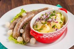 维也纳香肠用土豆沙拉和烂醉如泥的葱在一张木桌上 免版税库存照片