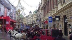 维也纳,奥地利- 12月、24个用马拉的支架和拥挤圣诞节装饰了旅游街道 免版税库存照片
