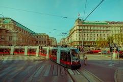 维也纳,奥地利- 2015年8月11日, :电车通过城市街道在一个美好的晴天,伟大的门面做它的方式 库存照片