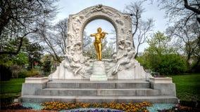 维也纳,奥地利- 2013年4月20日:弹一把小提琴的约翰・施特劳斯金黄雕象在Stadtpark 库存图片