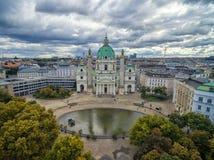 维也纳,奥地利- 2016年10月05日:有Resselpark公园和多云天空的维也纳Karlskirche教会 免版税库存图片
