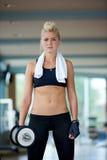 练习一些举重和工作在她的在健身房的二头肌 库存照片