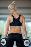 练习一些举重和工作在她的在健身房的二头肌 免版税库存图片